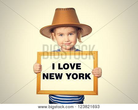 Little Funny girl in striped shirt with blackboard. Text welcome to New York. Isolated on a gray background.