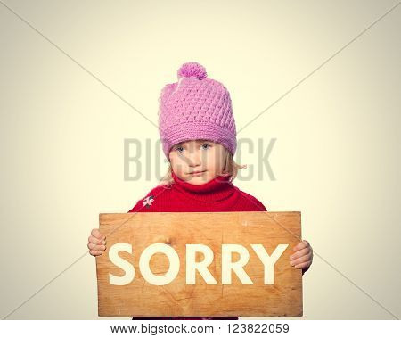 Little girl holding Board with inscription Sorry . Isolated on gray background