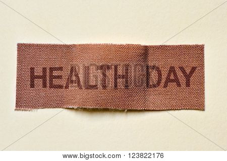 closeup of a fabric adhesive bandage with the text health day, on an off-white background