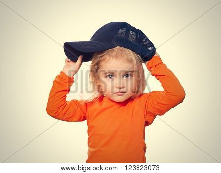 Little Funny girl in baseball cap and orange blouse. Isolated on gray background