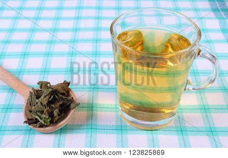 Healthy dried lemon balm with wooden spoon and glass of calming herbal drink on tablecloth sedative herbs concept for healthy nutrition and herbalism