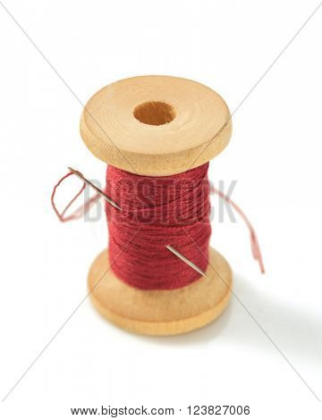spool of thread and needle isolated on white background