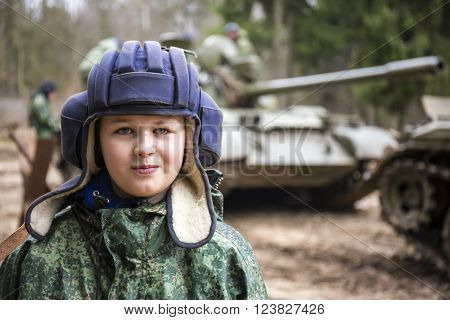 Teen boy in tank helmet and camouflage uniform with tanks on background