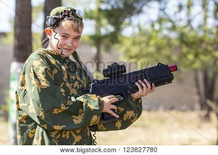 Teen boy with a gun in camouflage playing laser tag