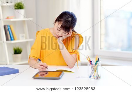 people, education, high school and learning concept - bored asian young woman student with tablet pc computer, book and notepad writing at home