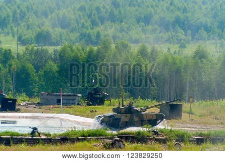 Nizhniy Tagil, Russia - July 12. 2008: Display of fighting opportunities of arms and military equipment. RAE exhibition. Tank T-80 leaves on soil after overcoming of water obstacle