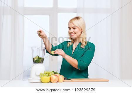healthy eating, cooking, vegetarian food, diet and people concept - smiling young woman putting fruits and vegetables into blender at home kitchen