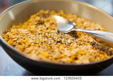 food, clean eating, healthy breakfast and diet concept - close up of bowl with granola or muesli and spoon on table