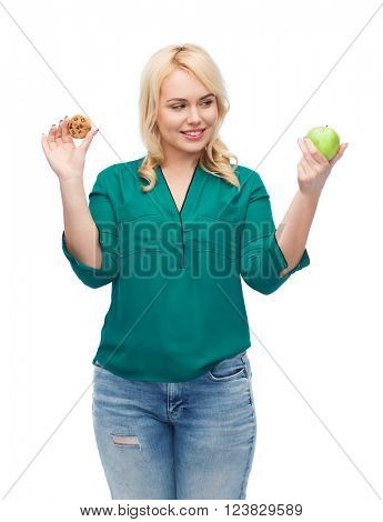 healthy eating, junk food, diet and choice people concept - smiling woman choosing between apple and cookie