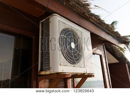 cooling, freshness and heat concept - close up of air conditioner at bungalow house outdoors