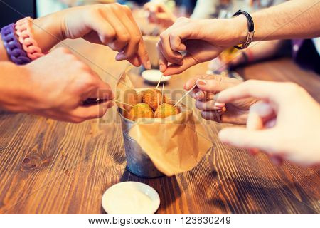 fast food, junk food, unhealthy eating and culinary concept - close up of people hands taking cheese balls with skewers at bar or restaurant