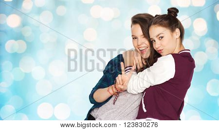 people, friends, teens and friendship concept - happy smiling pretty teenage girls hugging and showing peace hand sign over blue holidays lights background