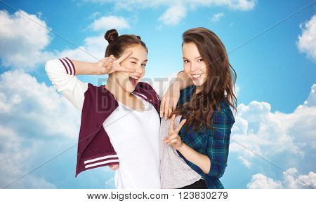 people, friends, teens and friendship concept - happy smiling pretty teenage girls showing peace hand sign over blue sky and clouds background