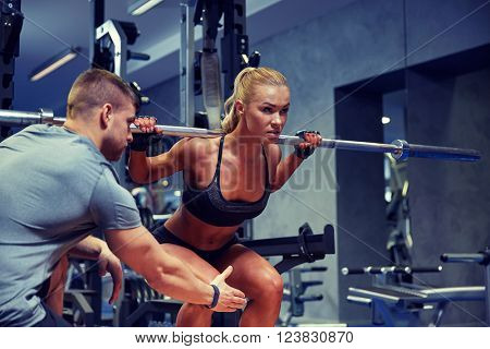 sport, fitness, teamwork, bodybuilding and people concept - young woman and personal trainer with bar flexing muscles in gym
