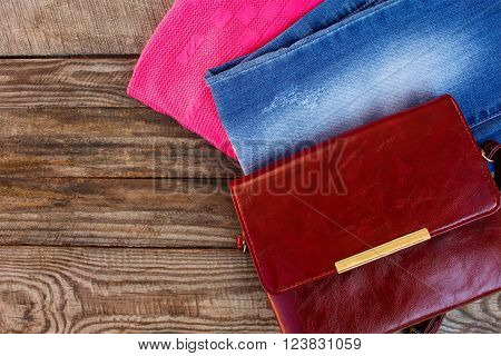 Women's clothing and accessories: sweater, jeans, handbag on wooden background. Toned image.