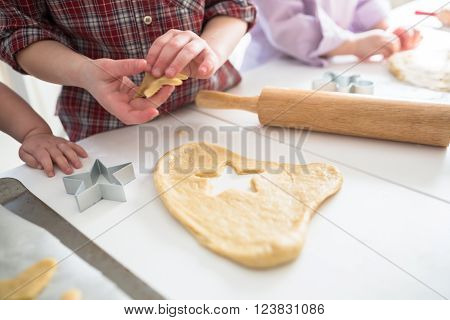 child making cookies on the kitchen table. Roll out the dough and molds to cut. Dough. Uncooked cookie.