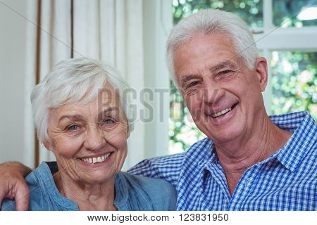 Close-up portrait of happy senior couple with arm around at home