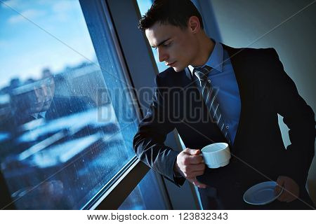 Thoughtful businessman drinking coffee and looking through the window at office