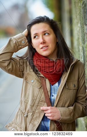 Brunette woman in red scarf and khaki jacket