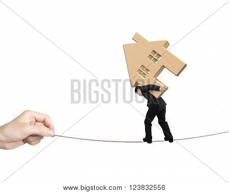 Man carrying wooden house and balancing on tightrope with hand pulling, isolated on white background.
