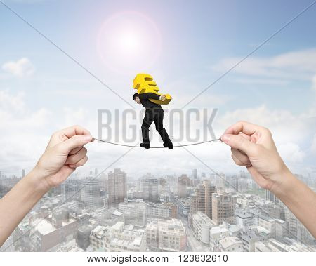 Man carrying golden Euro sign balancing on tightrope with woman hands holding two sides on cityscape background.