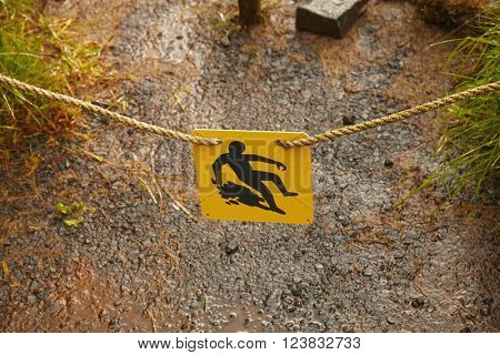 Slippery warning sign on mountain trail