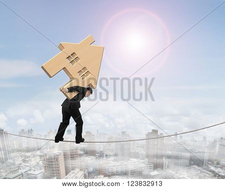 Man carrying wooden house and balancing on tightrope with sunny sky cityscape background.