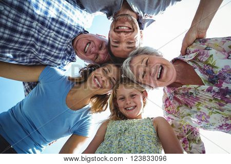 Cheerful family forming huddle in back yard against sky