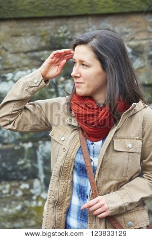 Young brunette shoot against stone wall, wear red scarf and khaki jacket