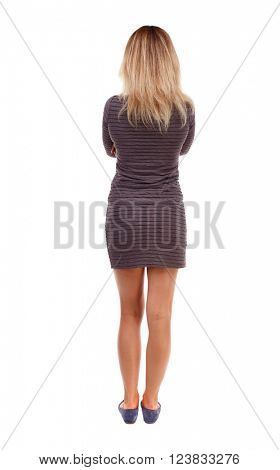 back view of standing young beautiful  woman.  girl  watching. Rear view people collection.  backside view of person. Folding his arms girl in brown dress looking ahead.