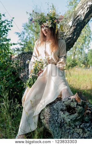 Attractive Woman Portrait in traditional clothes with Wreath of Flowers relaxing on birch. Ivan Kupala Holiday Celebration