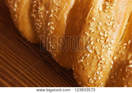 Bread bun with sesame seeds on the wooden table