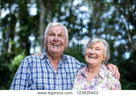 Happy senior man and woman looking up in back yard