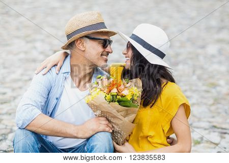 Happy couple looking at each other with bouquet while sitting outdoors
