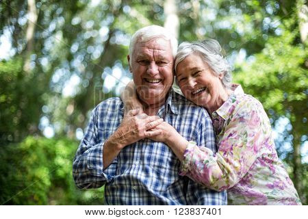 Happy senior woman embracing from behind husband against trees in back yard