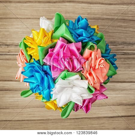 Bouqet of colorful decorative bows on the wooden background.
