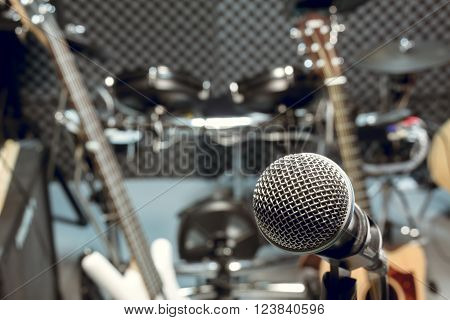 selective focus microphone and blur musical equipment guitar bass drum piano background.
