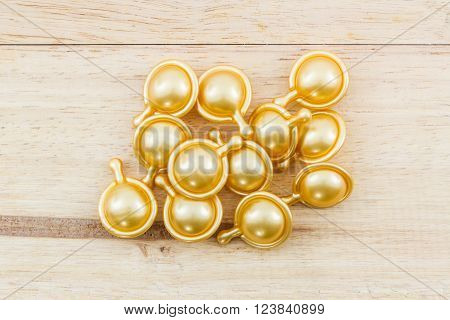 Hair vitamin serum capsule gold color on wood background.