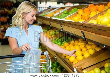 Smiling woman taking oranges at grocery shop while holding plastic bag
