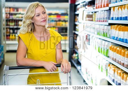 Blond woman pushing cart choosing products at supermarket