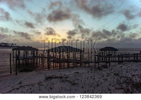 The setting sun illuminates the piers near Apalachicola Bay Florida USA