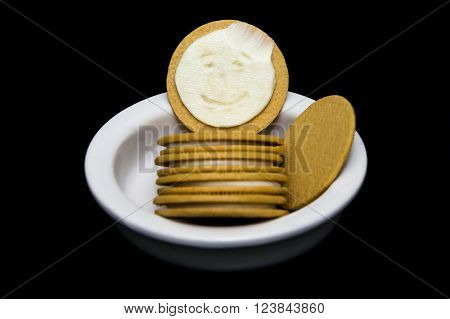 A licked cream filling face appears inside of a yellow cookie.