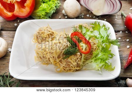 Restaurant food. Meat pate balls served with lettuce and cheese. Served at wooden rustic background with vegetables.