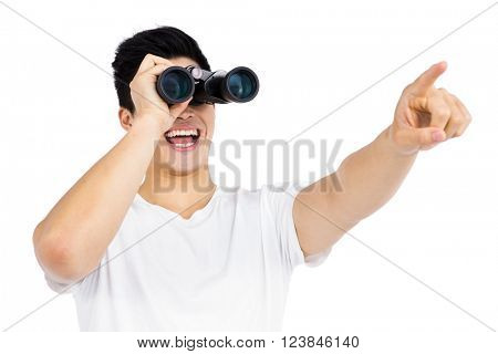 Young man looking through binocular on white background