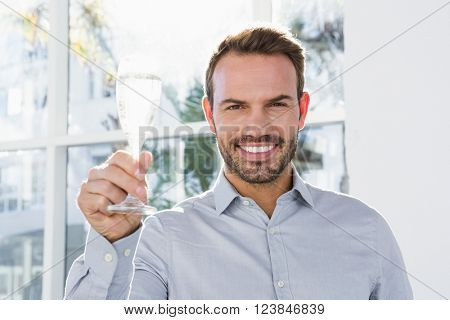 Happy young man holding a glass of champagne