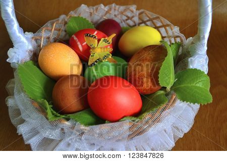 Easter eggs in a wicker basket with a tulle butterfly