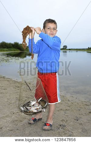 In the summer on the river boy holding a fish tank with fish roach.
