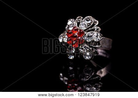 Silver jewelry with red stones inside on black background