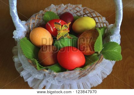 Easter eggs in a wicker basket in white tulle with butterfly