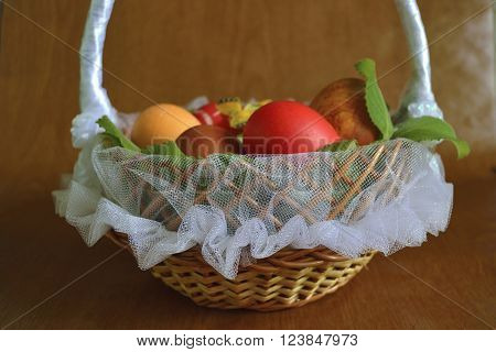 Easter eggs in a wicker basket with tulle and satin ribbons